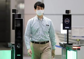 "July 13, 2020, Tokyo, Japan - An employee of Japan\'s electronics giant NEC demonstrates the new entrance gate which enables to recognize gusets\' faces with or not with face masks at NEC\'s headquarters in Tokyo on Monday, July 13, 2020. NEC introduces several technologies for the digital offices with biometrics to form the ""New Normal"" digitalization society. (Photo by Yoshio Tsunoda\/AFLO"
