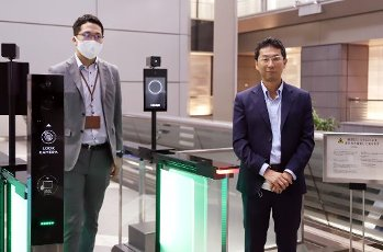 "July 13, 2020, Tokyo, Japan - Japan\'s electronics giant NEC fellow Hitoshi Imaoka (R) displays the new entrance gate which enables to recognize gusets\' faces with or not with face masks at NEC\'s headquarters in Tokyo on Monday, July 13, 2020. NEC introduces several technologies for the digital offices with biometrics to form the ""New Normal"" digitalization society. (Photo by Yoshio Tsunoda\/AFLO"
