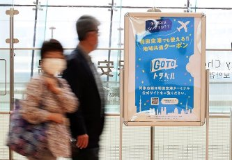 """October 1 2020, Tokyo, Japan - Tourists pass a notice board of governemnt\'s doestic travel campaign """"Go To Travel"""" at Tokyo\'s Haneda airport on Thursday, October 1, 2020 as Tokyo is included in the tourism promotion """"Go To Travel"""". (Photo by Yoshio Tsunoda\/AFLO"""