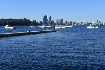 Landscape view of sail boats mooring on Swan River against Perth financial district skyline in Western Australia