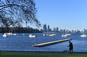 Silhouette of unrecognizable young adult Australian couple walking their dog along the Swan River against Perth financial district skyline in Western Australia