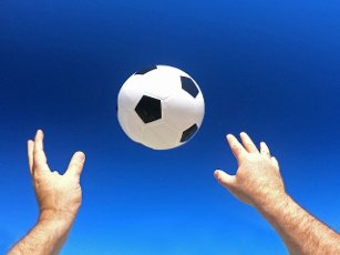Point of view (POV) of a person throwing a football in the air. Concept photo of achieving life goals. No people. Copy space