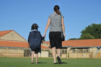 Rear view of a mother and young daughter holding hands walking together to school