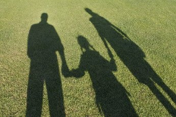 Shadow on green grass of two parents (father and mother) walking together daughter to school holding hands. Family relationship concept