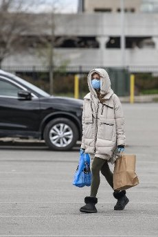 April 10, 2020: A shopper walks across the lot wearing a mask at The Shoprite in Jersey City, New Jersey. Mandatory credit: Kostas Lymperopoulos/