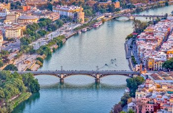 Aerial view of Triana (foreground) and San Telmo (background) bridges over the Guadalquivir river, Seville, Spain. High resolution vertical panorama
