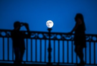 Couple taking pictures under moonling on the Triana bridge, Seville, Spain