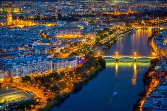 Aerial view of downtown Seville at night, showing some of the main landmarks: Triana bridge, Guadalquivir river, Cathedral, Giralda tower, Maestranza bullring, Torre del Oro, Plaza de España