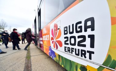16 April 2021, Thuringia, Erfurt: Participants of the press tour board a tram with the Buga logo in front of the grounds of the Federal Horticultural Show (BUGA) in egapark. From 23 April to 10 October 2021, the summer festival with horticultural showcase is to take place on two exhibition sites in Erfurt. In addition, 25 BUGA outdoor locations are planned throughout Thuringia. Photo: Martin Schutt\/dpa-Zentralbild\/ZB