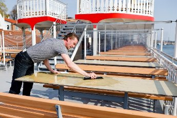 "19 April 2021, Schleswig-Holstein, Kappeln: Martin Neumann, employee on the paddle steamer ""Schlei Princess"" cleans the tables on deck. As participants in the ""Baltic Sea-Fjord-Schlei"" tourism model project, the passenger ships will be allowed to resume operations from 20 April 2021. Photo: Frank Molter\/dpa"
