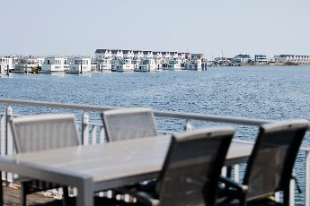 """19 April 2021, Schleswig-Holstein, Kappeln: A table with four chairs stands on a terrace at the Ostsee Resort Olpenitz on the Schlei. As a participant in the tourism model project """"Ostsee-Fjord-Schlei"""", the resort will once again be allowed to accommodate visitors in the holiday homes from 19 April 2021. Photo: Frank Molter\/dpa"""
