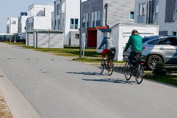 "19 April 2021, Schleswig-Holstein, Kappeln: Two holidaymakers cycle through the Baltic Sea resort Olpenitz on the Schlei. As a participant in the tourism model project ""Ostsee-Fjord-Schlei"", the resort will once again be allowed to accommodate visitors in the holiday homes from 19 April 2021. Photo: Frank Molter\/dpa"
