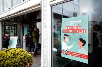 """14 May 2021, Lower Saxony, Norderney: A poster with the inscription """"Corona Schnelltest"""" (Corona rapid test) hangs in a window of the bathhouse at the Kurplatz, where the island\'s Corona test centre is currently located. In Lower Saxony, hotels, holiday apartments and other accommodation in regions with a seven-day incidence below 100 are once again allowed to receive guests. Photo: Hauke-Christian Dittrich\/dpa"""