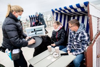 14 May 2021, Lower Saxony, Norderney: Waitress Nina (l) serves Anett and Christoph from near Oldenburg, who are sitting with their dog Murphy in a beach chair in front of the Surfcafe on the beach promenade. In Lower Saxony, hotels, holiday apartments and other accommodation in regions with a seven-day incidence of less than 100 are allowed to receive guests again. Photo: Hauke-Christian Dittrich\/dpa