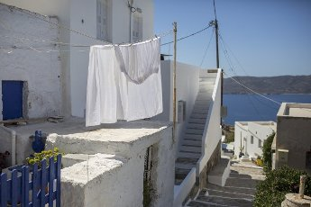 14 May 2021, Greece, Plaka: Curtains hang to dry in an alleyway on the Greek island of Milos. Saturday, May 15, marks the official start of the 2021 tourism season in Greece, when most of the previous Corona restrictions will fall away, including the ban on travel within the country. Tourism is an important economic factor for the country. Photo: Socrates Baltagiannis\/dpa