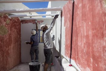 14 May 2021, Greece, Plaka: Two workers repair and paint the walls of the guest house on the Greek island of Milos. Saturday, May 15, marks the official start of the 2021 tourism season in Greece, when most of the previous Corona restrictions will fall away, including the ban on travel within the country. Tourism is an important economic factor for the country. Photo: Socrates Baltagiannis\/dpa