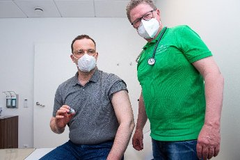 14 May 2021, North Rhine-Westphalia, Legden: Jens Spahn (l,CDU), Federal Minister of Health, holds a vial of AstraZeneca vaccine in Volker Schrage\'s (r) family practice. This is his first vaccination against the coronavirus. Photo: Guido Kirchner\/dpa