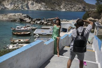 14 May 2021, Greece, Mandrakia: n woman poses for a fashion shoot on the Greek island of Milos. Saturday, May 15, marks the official start of the 2021 tourism season in Greece, when most of the previous Corona restrictions will be lifted, including the ban on travel within the country. Tourism is an important economic factor for the country. Photo: Socrates Baltagiannis\/dpa