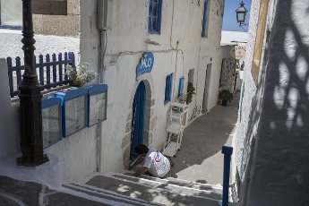 14 May 2021, Greece, Plaka: A man paints the stairs outside his restaurant on the Greek island of Milos. Saturday, May 15, marks the official start of the 2021 tourism season in Greece, when most of the previous Corona restrictions will fall away, including the ban on travel within the country. Tourism is an important economic factor for the country. Photo: Socrates Baltagiannis\/dpa