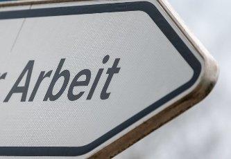 """06 May 2021, Saxony-Anhalt, Sangerhausen: """"Work"""" is written on a signpost in front of the employment agency in Sangerhausen. Photo: Hendrik Schmidt\/dpa-Zentralbild\/ZB"""