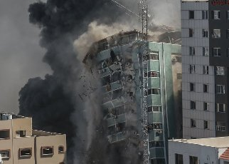 15 May 2021, Palestinian Territories, Gaza City: Al-Jalaa tower, which houses apartments and several media outlets, including The Associated Press and Al Jazeera, collapse after being hit by Israeli airstrikes, amid the escalating flare-up of Israeli-Palestinian violence. Photo: Mohammed Talatene\/dpa