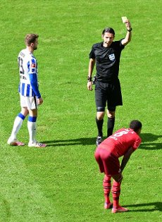 15 May 2021, Berlin: Football: Bundesliga, Hertha BSC - 1. FC Köln, Matchday 33 at Olympiastadion. Referee Deniz Aytekin shows Cologne\'s Ismail Jakobs the yellow card. IMPORTANT NOTE: In accordance with the regulations of the DFL Deutsche Fußball Liga and the DFB Deutscher Fußball-Bund, it is prohibited to use or have used photographs taken in the stadium and\/or of the match in the form of sequence pictures and\/or video-like photo series. Photo: Soeren Stache\/dpa-Pool\/dpa