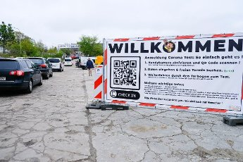 15 May 2021, Schleswig-Holstein, Eckernförde: The instructions for a Corona test are on a banner outside a drive-in station with cars lined up in front of it. Photo: Frank Molter\/dpa