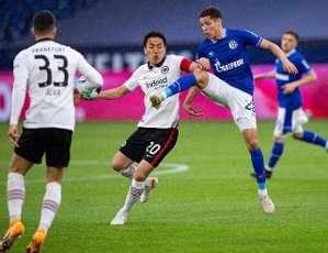 15 May 2021, North Rhine-Westphalia, Gelsenkirchen: Football: Bundesliga, FC Schalke 04 - Eintracht Frankfurt, Matchday 33 at Veltins Arena. Schalke\'s Amine Harit (r) and Frankfurt\'s Makoto Hasebe fight for the ball. Photo: Guido Kirchner\/dpa - IMPORTANT NOTE: In accordance with the regulations of the DFL Deutsche Fußball Liga and\/or the DFB Deutscher Fußball-Bund, it is prohibited to use or have used photographs taken in the stadium and\/or of the match in the form of sequence pictures and\/or video-like photo series