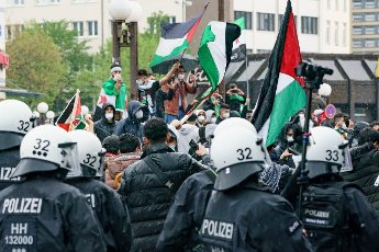 15 May 2021, Hamburg: Demonstrators hold Palestinian flags in front of approaching police forces at Altona station during a demonstration against Israeli actions in the current conflict in the Middle East. Photo: Axel Heimken\/dpa
