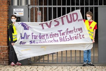 """12 June 2021, Bremen: Demonstrators stand shortly before the start of the Bremen SPD state party conference with a banner in their hands reading """"TVSTUD Bremen - We demand a collective agreement for student assistants"""" in front of the BLG Forum, where the party conference is taking place. Photo: Mohssen Assanimoghaddam\/dpa"""