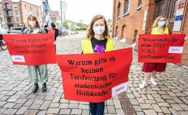 """12 June 2021, Bremen: Demonstrators stand shortly before the start of the Bremen SPD state party conference with placards in their hands reading """"Why do so few women have professorships; Why is there no collective agreement for student assistants; Science Plan 2025 - FULLY fund"""" in front of the BLG Forum, where the party conference is taking place. Photo: Mohssen Assanimoghaddam\/dpa"""