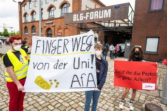 12 June 2021, Bremen: Demonstrators with posters and banners in their hands stand in front of the BLG Forum, where the party conference is taking place, shortly before the start of the SPD state party conference in Bremen. Photo: Mohssen Assanimoghaddam\/dpa