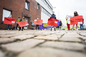12 June 2021, Bremen: Demonstrators with placards in their hands stand in front of the BLG Forum, where the SPD state party conference in Bremen is taking place, shortly before it begins. Photo: Mohssen Assanimoghaddam\/dpa