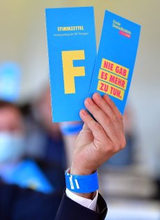 12 June 2021, Thuringia, Erfurt: A delegate holds voting cards during a vote at the state party convention of the Thuringian FDP. The party wants to elect its new party leadership on this day. Photo: Martin Schutt\/dpa-Zentralbild\/dpa