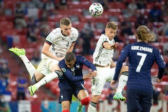 15 June 2021, Bavaria, Munich: Football: European Championship, France - Germany, preliminary round, Group F, 1st matchday in the EM Arena Munich. Germany\'s Matthias Ginter (l) and Joshua Kimmich (r) and France\'s Kylian Mbappe fight for the ball. Photo: Federico Gambarini\/dpa
