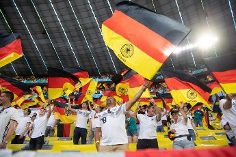 15 June 2021, Bavaria, Munich: Football: European Championship, France - Germany, preliminary round, Group F, 1st matchday in the EM Arena Munich. German fans wave flags before the match. Photo: Federico Gambarini\/dpa