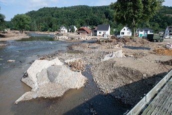 27 July 2021, Rhineland-Palatinate, Insul: Remains of the arched bridge swept away by the flood lie in the waters of the Ahr. Helpers are busy day and night to make the roads in the largely destroyed villages passable again. Photo: Boris Roessler\/dpa