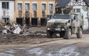 27 July 2021, Rhineland-Palatinate, Altenahr: A dingo of the Bundeswehr drives through the streets destroyed after the flood disaster. Helpers are busy day and night making the roads in the largely destroyed villages passable again. Photo: Boris Roessler\/dpa