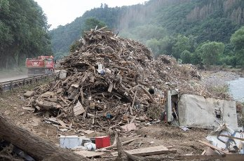 27 July 2021, Rhineland-Palatinate, Altenahr: Flotsam and rubbish pile up metres high on the side of a main road. Helpers are working day and night to make the roads in the largely destroyed villages passable again. Photo: Boris Roessler\/dpa