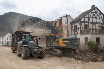 27 July 2021, Rhineland-Palatinate, Altenahr: Workers use an excavator to demolish a house destroyed by the flood. Helpers are busy day and night making the roads in the largely destroyed villages passable again. Photo: Boris Roessler\/dpa