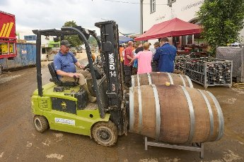 27 July 2021, Rhineland-Palatinate, Ahrweiler: Volunteers are busy at the Adeneuer wine estate cleaning up the cellar and the bottles covered with mud by the flood. In the Ahr valley, which was severely devastated by the flood, the cleanup work continues unabated. Photo: Thomas Frey\/dpa