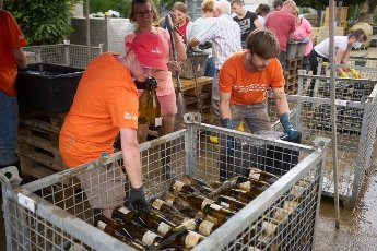 27 July 2021, Rhineland-Palatinate, Ahrweiler: Volunteers are busy at the Adeneuer winery cleaning the bottles covered with mud by the flood. In the Ahr valley, which was heavily devastated by the floods, the cleanup work continues unabated. Photo: Thomas Frey\/dpa