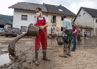 dpatop - 27 July 2021, Rhineland-Palatinate, Altenahr: With a human chain, helpers scoop mud out of a cellar. Helpers are busy day and night making the roads in the largely destroyed villages passable again. Photo: Boris Roessler\/dpa