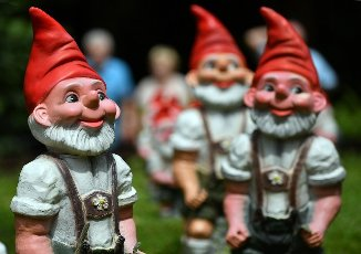 27 July 2021, Thuringia, Trusetal: Visitors tour garden gnomes at the gnome park. The Dwarf Park celebrates the 25th anniversary of its existence this year. More than 2,500 garden gnomes in various sizes are created on an area of around 5,000 square metres. In addition to the open-air exhibition, there is also the Thuringian Garden Gnome Museum, which deals with the history of garden gnomes. Photo: Martin Schutt\/dpa-Zentralbild\/dpa