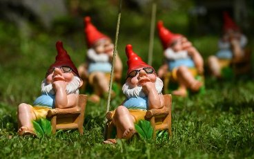 """27 July 2021, Thuringia, Trusetal: A group of garden gnomes """"sunbathing"""" in the gnome park. The gnome park celebrates the 25th anniversary of its existence this year. Over 2500 garden gnomes in various sizes are bred on an area of around 5000 square metres. In addition to the open-air exhibition, there is also the Thuringian Garden Gnome Museum, which deals with the history of garden gnomes. Photo: Martin Schutt\/dpa-Zentralbild\/dpa"""