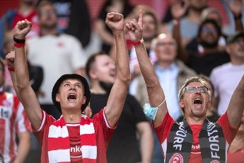 31 July 2021, North Rhine-Westphalia, Duesseldorf: Football: 2nd Bundesliga, Fortuna Düsseldorf - SV Werder Bremen, Matchday 2 at Merkur Spiel-Arena. Two Düsseldorf fans cheer on their team. Photo: Marius Becker\/dpa - IMPORTANT NOTE: In accordance with the regulations of the DFL Deutsche Fußball Liga and\/or the DFB Deutscher Fußball-Bund, it is prohibited to use or have used photographs taken in the stadium and\/or of the match in the form of sequence pictures and\/or video-like photo series