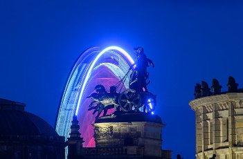 """31 July 2021, Saxony, Dresden: The observation Ferris wheel """"Wheel of Vision"""" turns in the evening on the Postplatz behind the Quadriga of the Semper Opera House. The 55-metre-high Ferris wheel will spin in the state capital until 3 October 2021. Photo: Robert Michael\/dpa-Zentralbild\/dpa"""