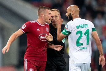 31 July 2021, North Rhine-Westphalia, Duesseldorf: Football: 2nd Bundesliga, Fortuna Düsseldorf - Werder Bremen, Matchday 2 at Merkur Spiel-Arena. Düsseldorf\'s Rouwen Hennings (l) and Bremen\'s mer Toprak (r) clash. In the middle, assistant referee Arno Blos. Photo: Marius Becker\/dpa - IMPORTANT NOTE: In accordance with the regulations of the DFL Deutsche Fußball Liga and\/or the DFB Deutscher Fußball-Bund, it is prohibited to use or have used photographs taken in the stadium and\/or of the match in the form of sequence pictures and\/or video-like photo series