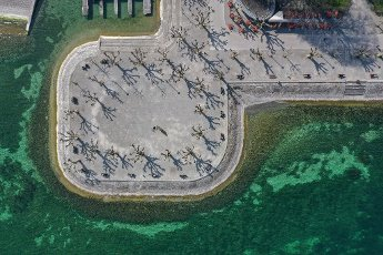 28 March 2020, Baden-Wuerttemberg, Konstanz: Some people sit on the benches on the shore of Lake Constance. (aerial photo with drone). It
