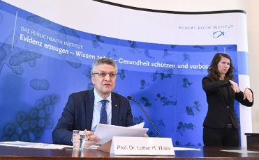 31 March 2020, Berlin: Lothar Wieler, head of the Robert Koch Institute, speaks at a press conference about the current status of the spread of the coronavirus and its control; a sign language interpreter (r) translates his words. Photo: Annegret Hilse/Reuters-Pool/
